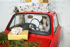 Women driving a car with Christmas gifts Royalty Free Stock Photography
