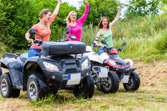 Women driving off-road with quad bike or ATV Stock Images