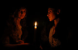 Women on each side of candle in the dark. Serious girls around burning candle in the dark, side view Stock Photos