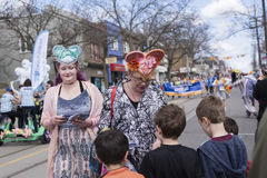 Women in Easter costume distribute gifts to children along the Queen Street East in the Beaches Easter Parade 2017 Stock Photos