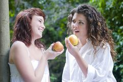 Women eating an apple and laughing Stock Images