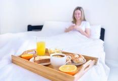 Women eating breakfast in bed Stock Photo