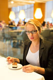 Women eating dessert in fancy restaurant. Royalty Free Stock Photography