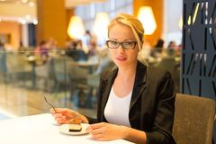 Women eating dessert in fancy restaurant. Royalty Free Stock Image
