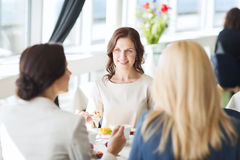 Women eating dessert and talking at restaurant. People, food, communication and lifestyle concept - happy women eating dessert and talking at restaurant Royalty Free Stock Photography