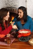Women eating fondue. Photo of two beautiful females dipping bread into the melted cheese in a fondue pot. Focus is on girl on the right stock photo