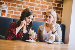 Women eating healthy dessert in a restaurant. Two women consuming sweet healthy dessert in a restaurant, talking and spending time together. Clean eating Royalty Free Stock Photo