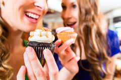 Women eating muffins while coffee drinking Royalty Free Stock Images