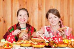 Women eating pancake during Shrovetide stock photos