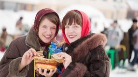 Women eating pancake during Shrovetide royalty free stock images