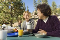 Women eating at picnic table in campground Stock Photos