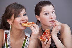 Women eating pizzas Royalty Free Stock Photos