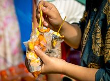 Women are eating roasted squid with seafood sauce in clear plastic bag along with ice cream Royalty Free Stock Photography
