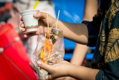 Women are eating roasted squid with seafood sauce in clear plastic bag along with ice cream Stock Images