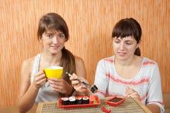 Women eating sushi rolls royalty free stock image