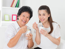 Women eating yogurt. Eating yogurt. Happy Asian family eating yoghurt at home. Beautiful senior mother and adult daughter, healthcare concept Stock Photos