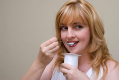 Women eats yoghurt royalty free stock photos