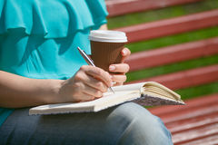 Women and education, close up of hands of girl studying for coll. Ege exam in park. Side view Stock Photography