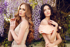 Women  in elegant dresses, posing in blossom spring garden Stock Photo