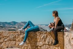 Women embrace and laugh while sitting on the castle stone. Two happy smiling young people friends outdoor. Two women on the castle stone stock image