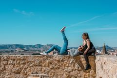 Women embrace and laugh while sitting on the castle stone royalty free stock image