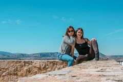 Women embrace and laugh while sitting on the castle stone. Two happy smiling young people friends outdoor. Two women on the castle stone stock photo