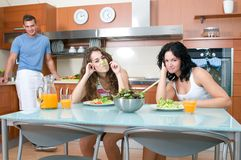 Women enjoying her salad and man in the kitchen Royalty Free Stock Images