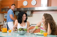 Women enjoying her salad and man in the kitchen Stock Photos