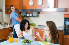 Women enjoying her salad and man in the kitchen Stock Photo