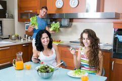 Women enjoying her salad and man washing Stock Photos