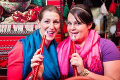 Women enjoying hookah or shisha in oriental cafe Stock Images