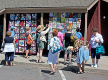 Women Enjoying Outdoor Quilt Show. Women enjoying and photographing quilts hanging on a building at the 2011 outdoor quilt show in Sisters, Oregon Stock Image