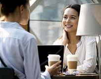 Women enjoying some morning coffee at coffee shop Royalty Free Stock Photos