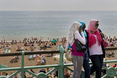 Women enjoying the sun in Brighton. BRIGHTON, UNITED KINGDOM - CIRCA JULY 2009: Tourists run to Brighton every year to enjoy the summer heat.  The beach is Stock Photos