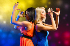 Women in evening dresses dancing in the club Stock Photo