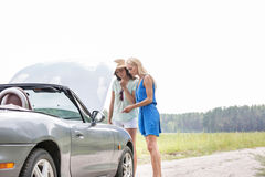 Women examining broken down car on sunny day against clear sky Royalty Free Stock Photo