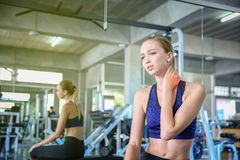 Women exercise already painful. Young caucasian female having pain in her neck while workout at the gym. Woman feeling strong pain. In muscles after exercising royalty free stock images