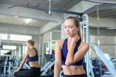 Women exercise already painful. Young caucasian female having pain in her neck while workout at the gym. Woman feeling strong pain. In muscles after exercising stock images
