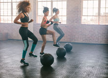 Women exercising in aerobics class. Young women exercising in aerobics class with medicine balls on floor. Three females doing workout together in gym stock images