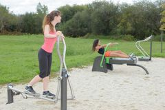 Women exercising on sport machine in outdoor gym. Women exercising on a sport machine in outdoor gym Royalty Free Stock Photography