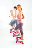 Women exercising on stepping machine. Group of women doing exercise on stepper. They're looking at camera. Side view Stock Photos