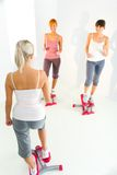 Women exercising on stepping machine. Group of women doing exercise on stepper. High angle view Stock Images