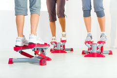Women exercising on stepping machine. Group of women doing exercise on stepper. Closeup on legs. Low angle view Royalty Free Stock Photography