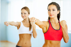 Women exercising. Two beautiful young women in sports clothing exercising and looking away Royalty Free Stock Photo