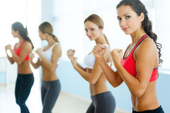 Women exercising. Two beautiful young women in sports clothing exercising and looking at camera Stock Photography