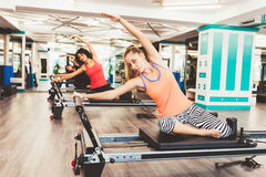 Women exercising. View of women exercising on reformer bed at gym Stock Photos