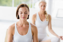 Women with eyes closed doing yoga. At fitness studio royalty free stock images