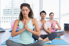 Women with eyes closed and joined hands at fitness studio Stock Photo