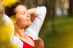 Women with eyes closed smiling. Portrait of a young beautiful woman with eyes closed smiling in a sunny spring day royalty free stock photos