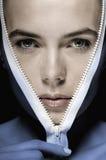 Women face. Beautiful women face coming out of zipper Stock Image